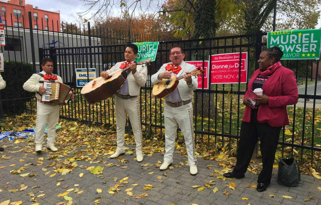 Dionne Reeder and three musicians in a mariachi band standing with fall leaves on the ground.