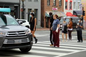 A driver makes a left turn as pedestrians cross the crosswalk.