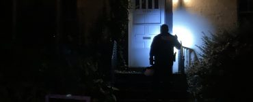 Police officer shines a flashlight on home