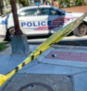 Police tape and cruiser blocking street