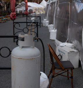 Propane heaters just up against the walls of a plastic tent.