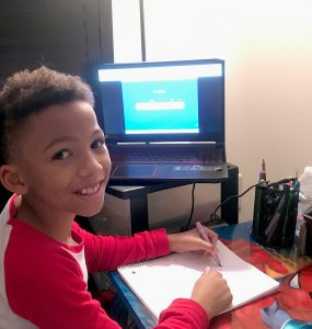 Antonio Malik sits at his desk where he attends online classes